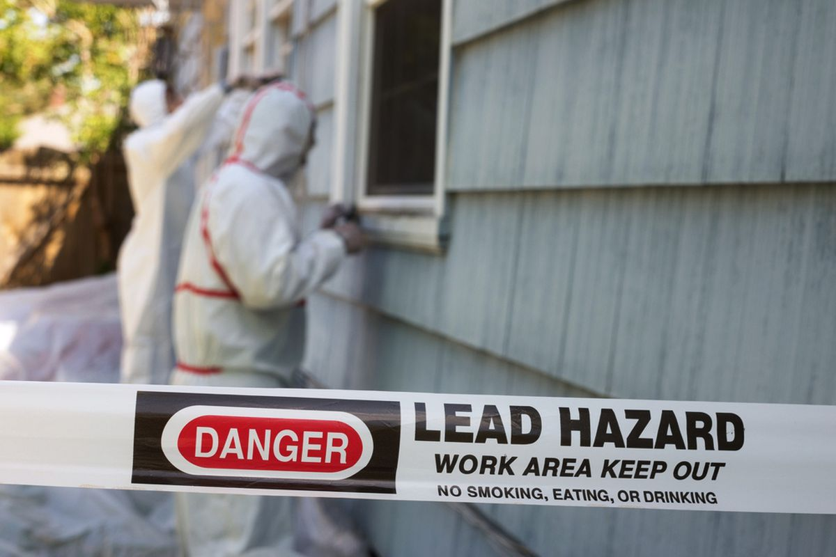 Workers in hazmat suits stripping lead paint from the side of a house.