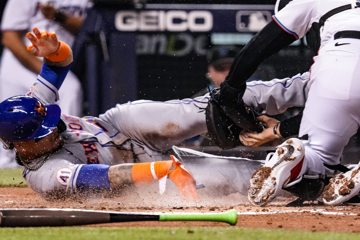Javier Báez #23 of the New York Mets slides into home plate to score a run against Alex Jackson #23 of the Miami Marlins in the second inning at loanDepot park