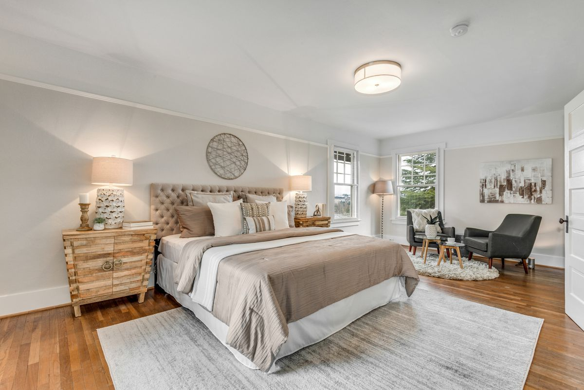 A bedroom with a beige coverlet, gray rug, and a small seating area next to it.