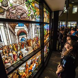 """The crowd looks at the stained glass after the unveiling of the """"Roots of Knowledge"""" in the Fulton Library on the Utah Valley University campus in Orem on Friday, Nov. 18, 2016."""