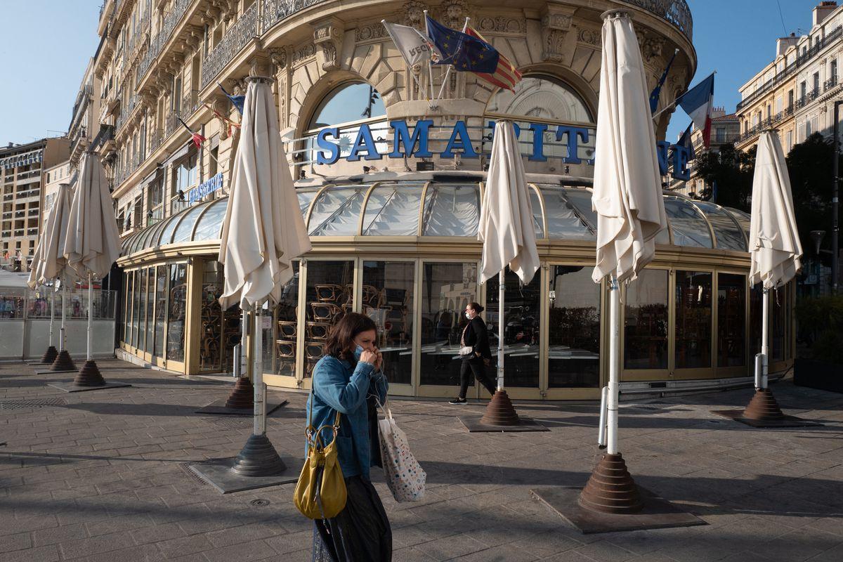 A woman walks in front of a shuttered restaurant facade.