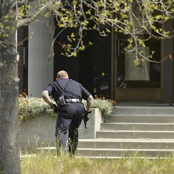 An Oakland police officer approaches the entrance to Oikos University in Oakland, Calif., Monday, April 2, 2012. A suspect was detained Monday in a shooting attack at a California Christian university that sources said has left at least five people dead.