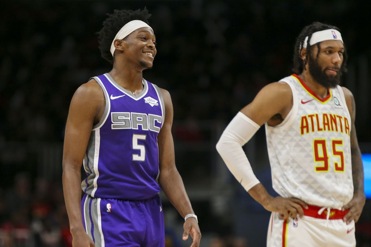Sacramento Kings guard De'Aaron Fox and Atlanta Hawks guard DeAndre' Bembry on the court in the third quarter at State Farm Arena.