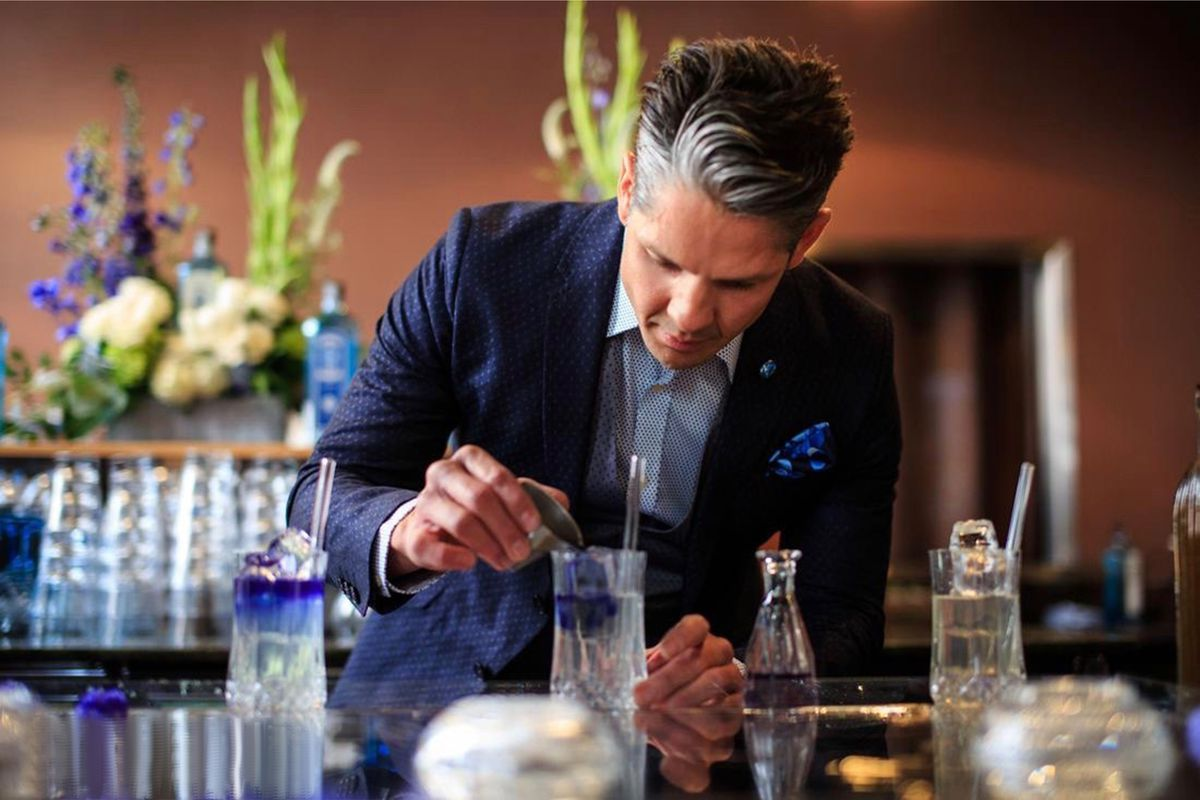 In a blue jacket and blue spotted jacket, bartender Estanislado Orona applies butterfly pea flower to a drink.