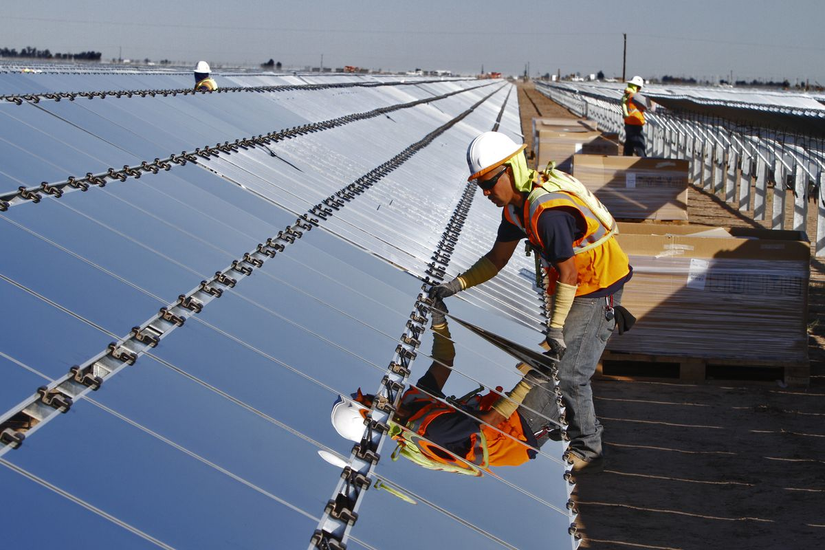 A worker installs a photovoltaic panel at the Tenaska Imperial Solar Energy South project in California.
