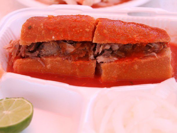 A split torta ahogada laced with spicy sauce in a takeout container.