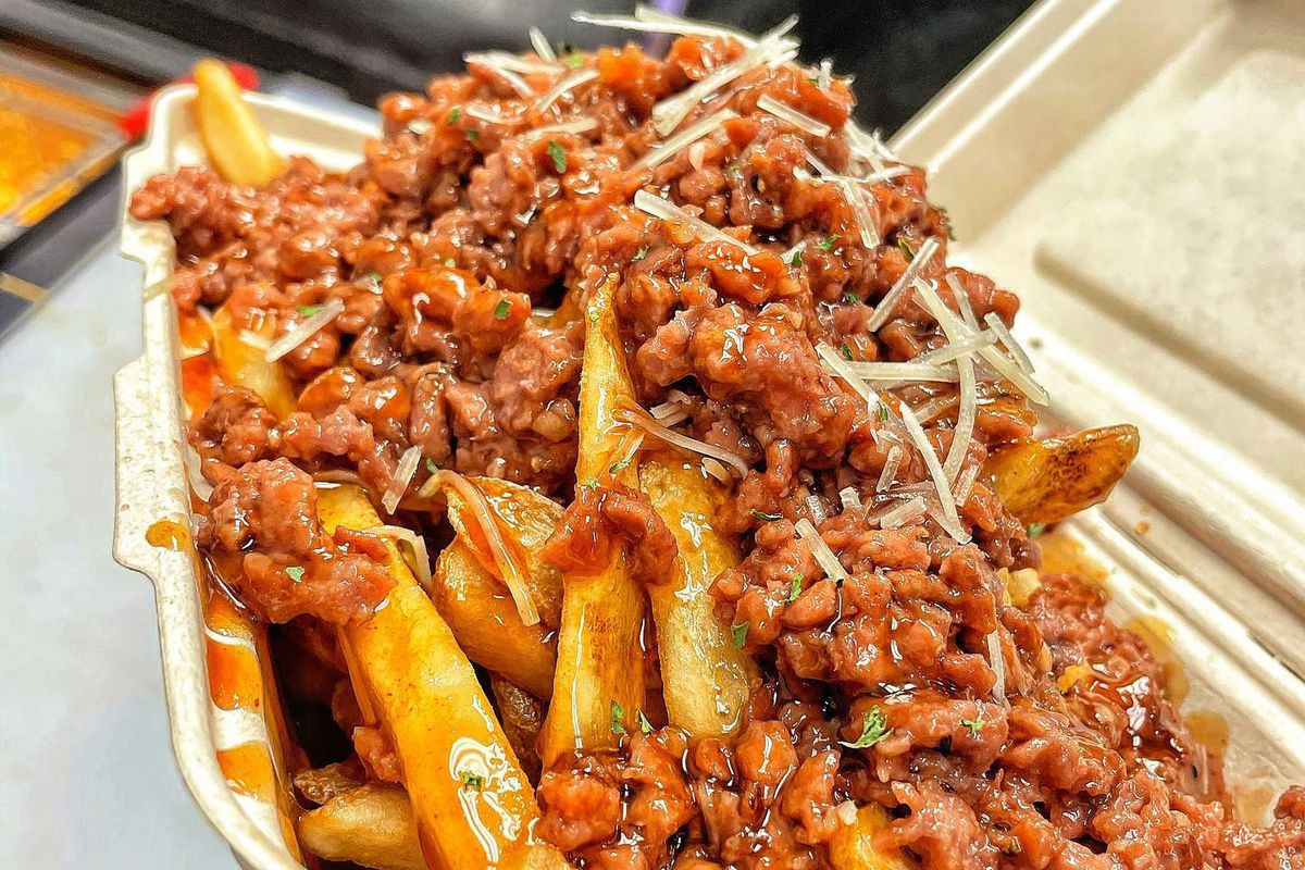 A takeout container overflowing with French fries topped with chili and cheese
