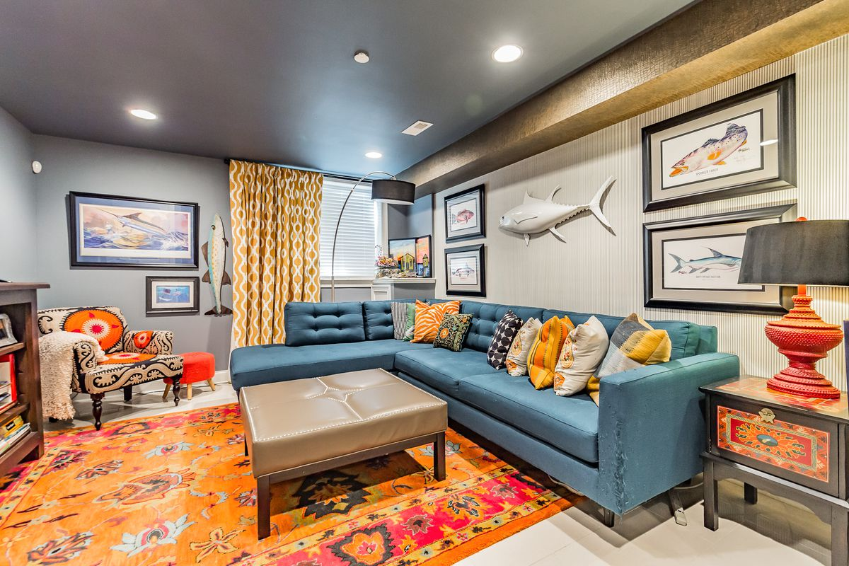 A colorful finished basement with a blue L-shaped couch, gray walls.