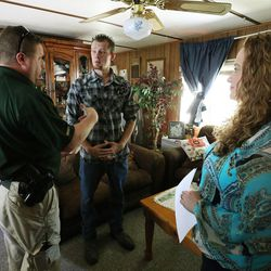 Salt Lake County deputy sheriff Jason Berg, left, and Jeannie Ybarra, of Salt Lake County Criminal Justice Services, right, talk with Intensive Supervision client Shawn Myers, center, at his home in Salt Lake City on Thursday, Oct. 6, 2016.