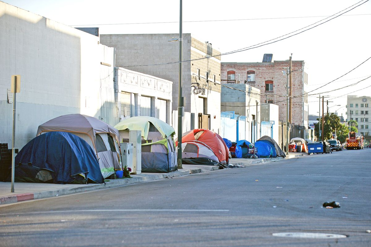 A row of tents on a sidewalk in an industrial city space