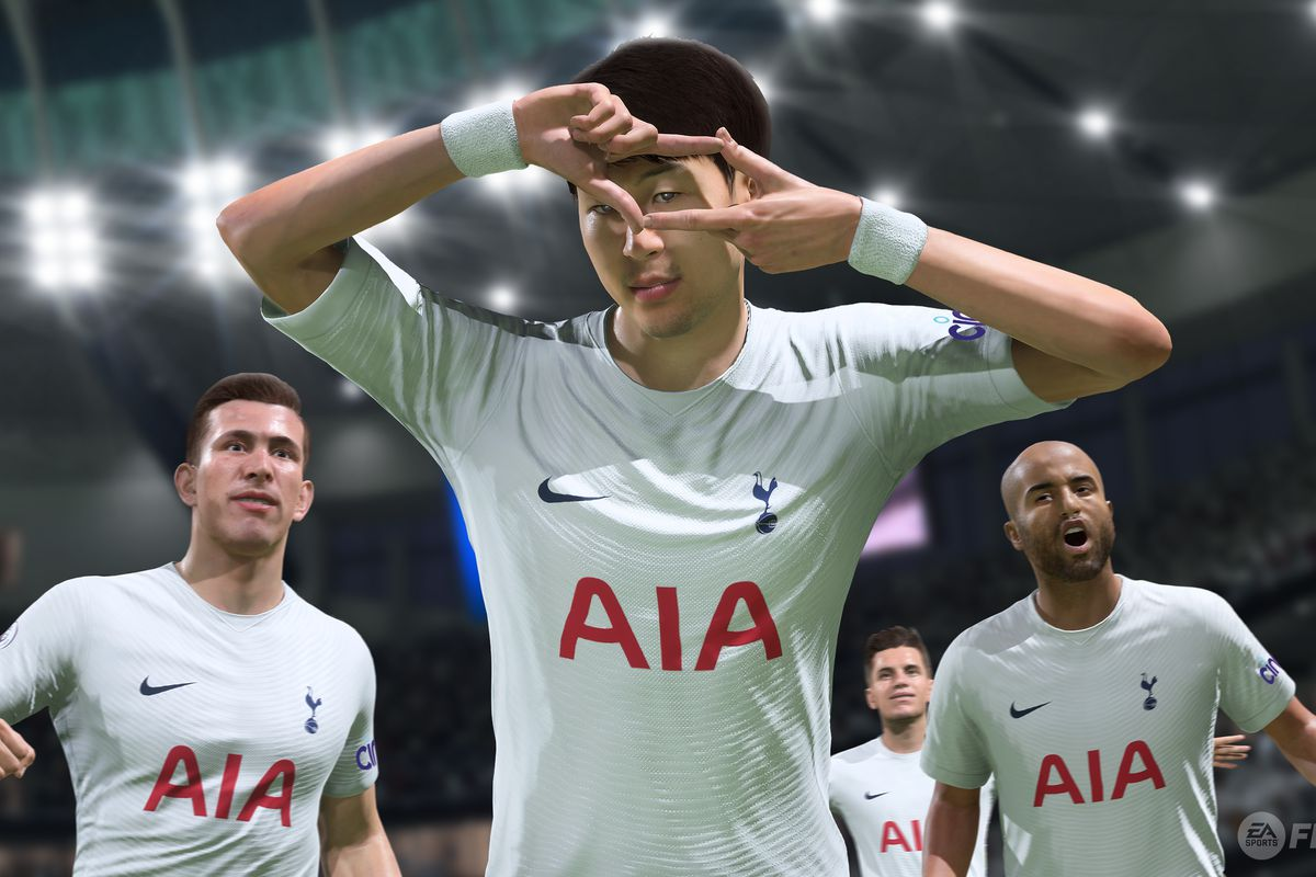Son Heung-min of Tottenham celebrates a goal in FIFA 22 by making a movie-frame gesture over his left eye. Two teammates are joining the celebration from behind.
