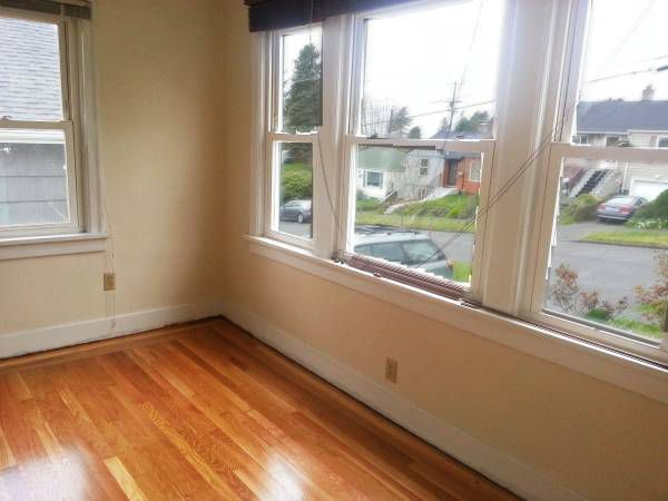 A corner room with hardwood floors and windows on two walls