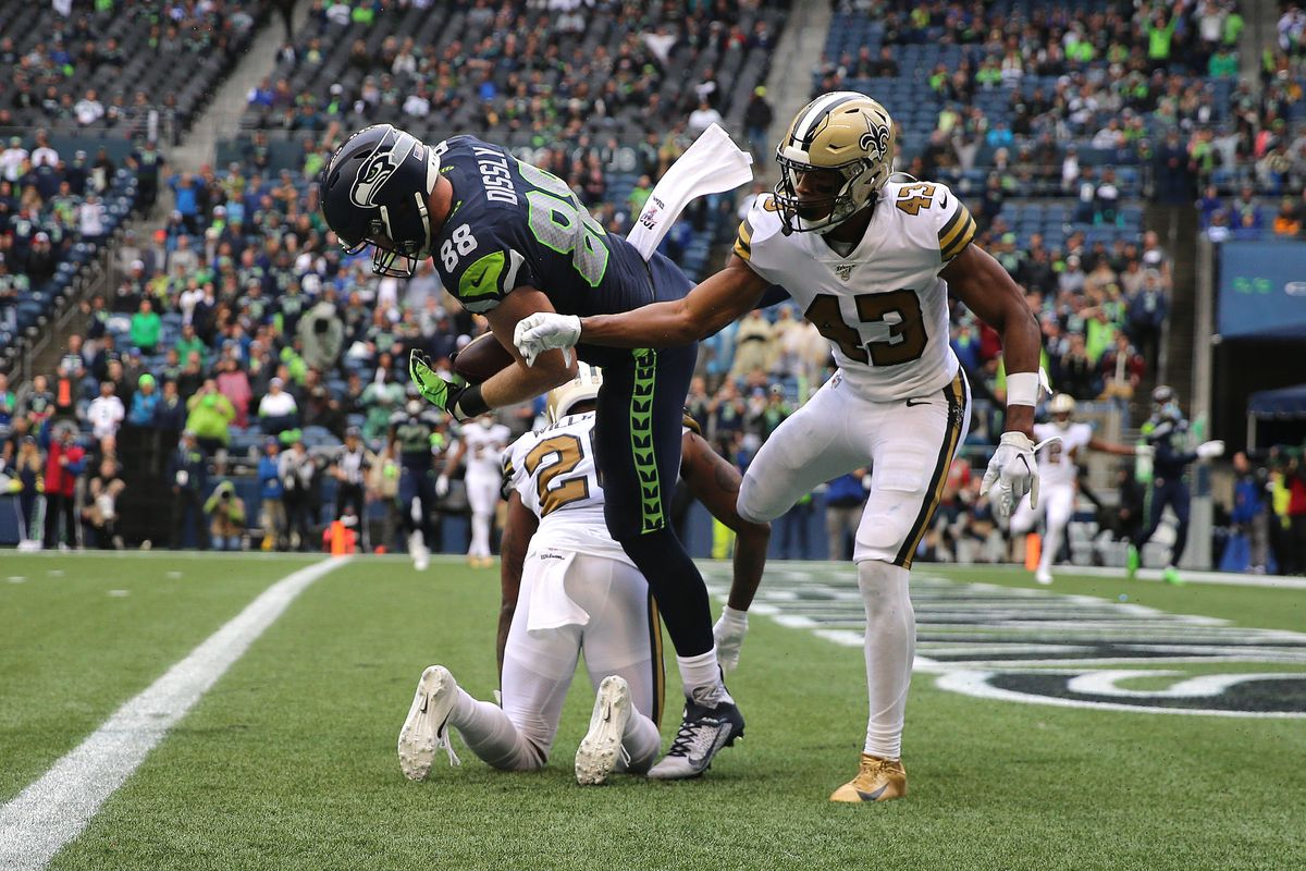 Will Dissly of the Seattle Seahawks completes a four yard touchdown pass against Marcus Williams of the New Orleans Saints in the fourth quarter during their game at CenturyLink Field on September 22, 2019 in Seattle, Washington.