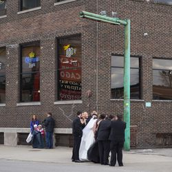 Wedding party taking a photo in front of Cubby Bear, on the Addison Street side, with the marquee behind them