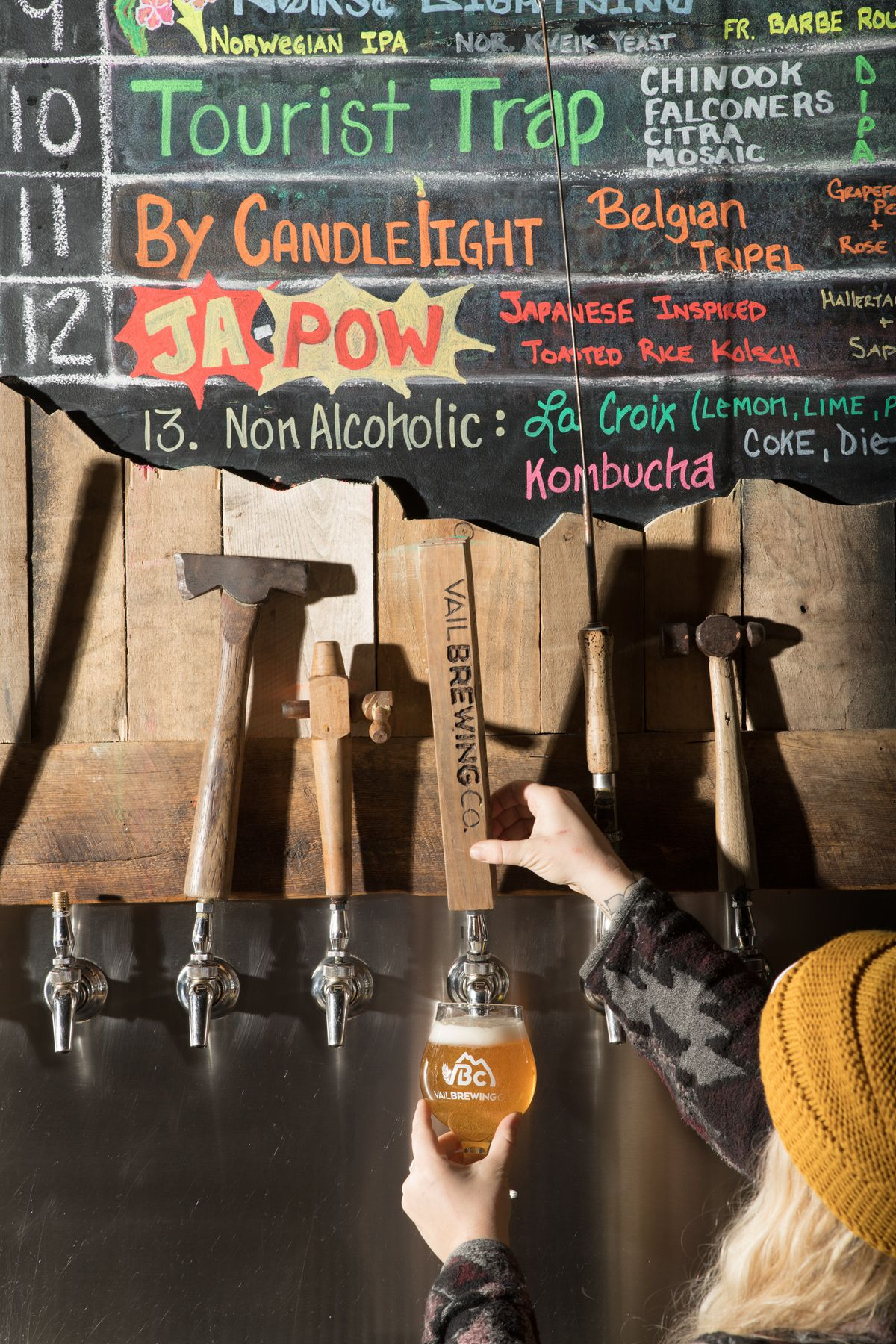 A woman pouring a beer from the tap at Vail Brewing Co.