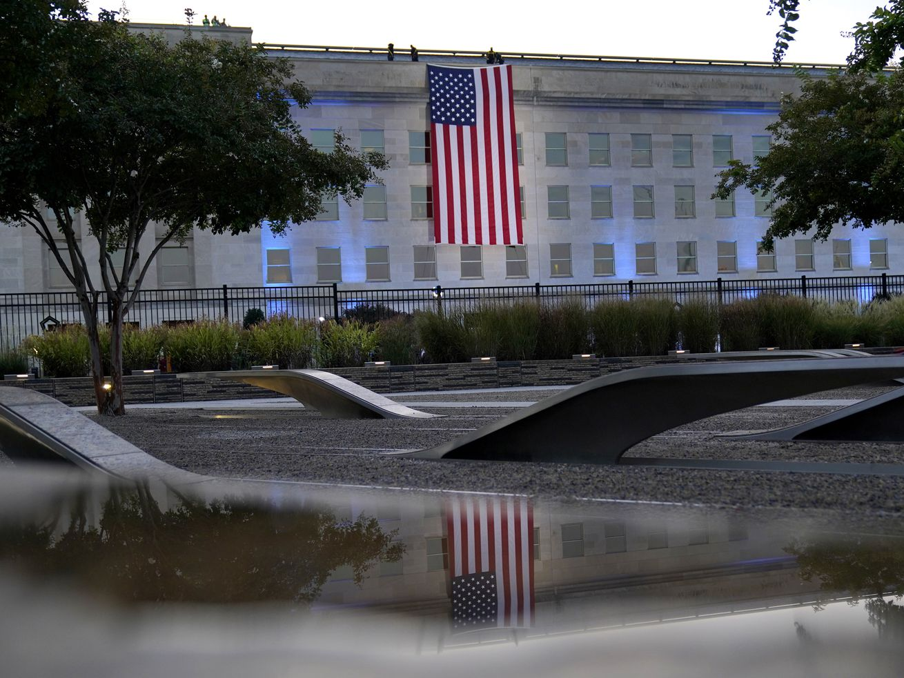 An American flag is unfurled at the Pentagon in Washington, Saturday, Sept. 11, 2021, at sunrise on the morning of the 20th anniversary of the terrorist attacks. The American flag is draped over the site of impact at the Pentagon. In the foreground, the National 9/11 Pentagon Memorial, opened in 2008 adjacent to the site, commemorates the lives lost at the Pentagon and onboard American Airlines Flight 77..