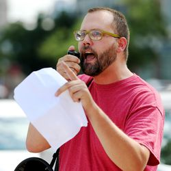 Organizer David Newlin speaks to a small group of activists gathered at the Wallace F. Bennett Federal Building in Salt Lake City to protest President Donald Trump and war on Saturday, Aug. 19, 2017.