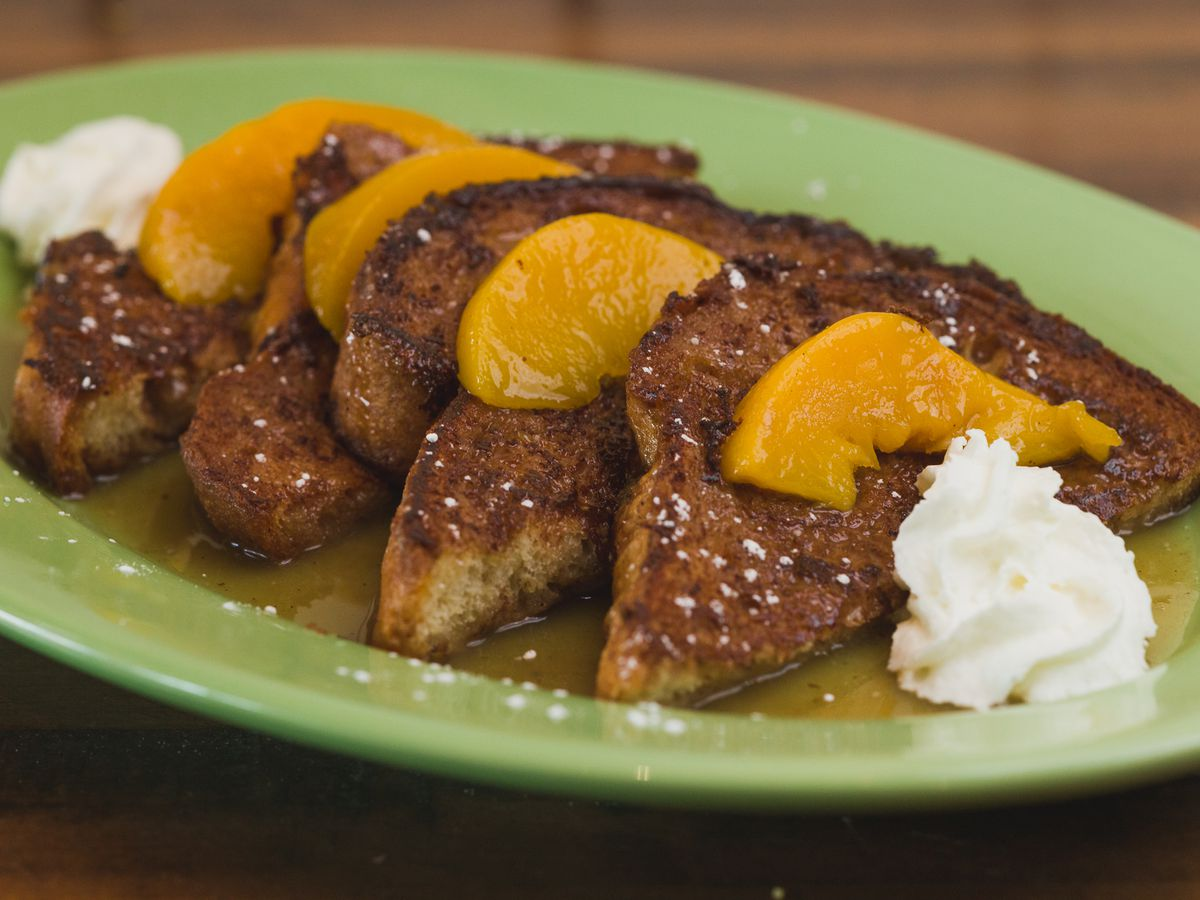 French toast cut in quarters on a plate with peach slices on top and dollops of whipped cream