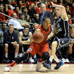 Utah Utes guard Brandon Taylor (11) draws the foul driving to the basket as Brigham Young Cougars guard Skyler Halford (23) defends during a game at the Jon M. Huntsman Center on Saturday, Dec. 14, 2013.