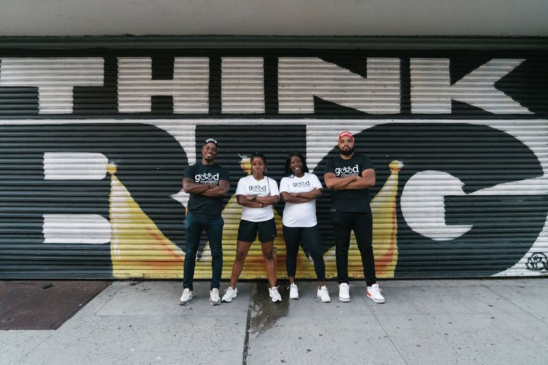 "Four people standing in front of a mural that says ""Think Big."""