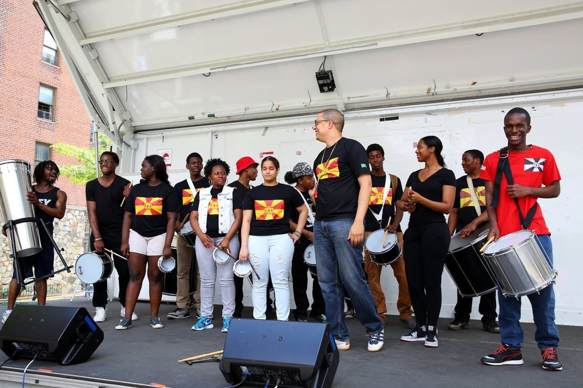 Students and members of Harlem Samba stand with their percussion instruments on a stage, most of them wearing black shirts with red and yellow flags.