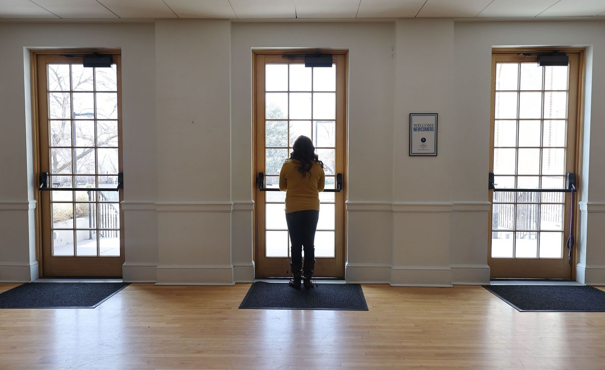 Vicky Chavez, who for three years has sought sanctuary with her young daughters at the First Unitarian Church of Salt Lake City, looks out of a door at the church on Wednesday, March 24, 2021. Chavez and three other women in similar situations in other states are suing U.S. immigration officials, alleging they are facing steep fines because they spoke out about their cases.