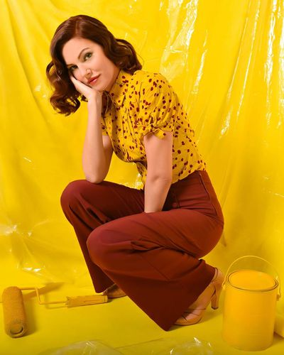 A model in red pants and a vintage button-down shirt against a yellow background