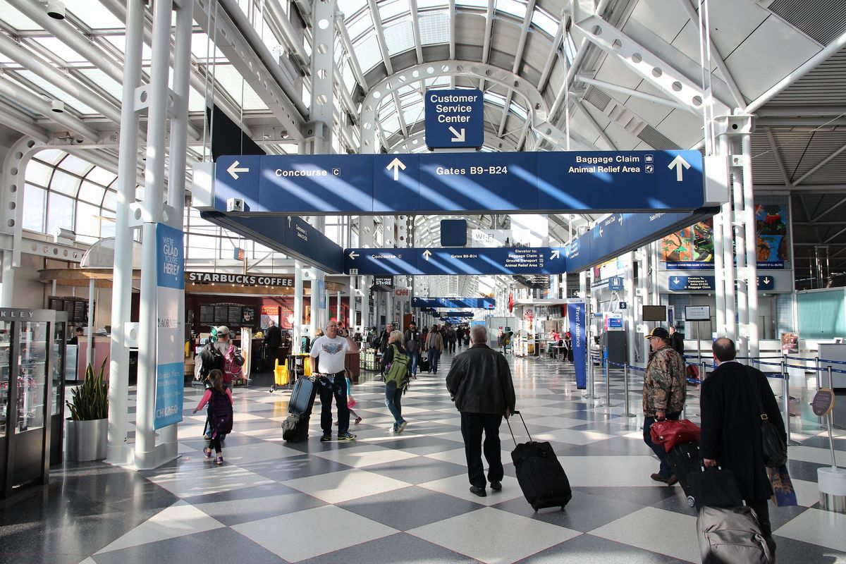 The interior of the Chicago O'Hare airport. There is a grey and white checkered floor. The ceiling is glass with white support beams. There are people walking with luggage.