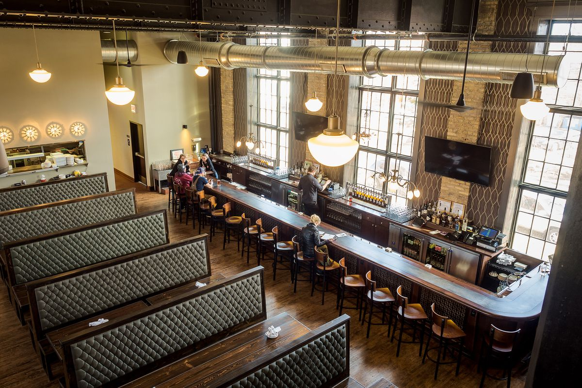 A vast dining room with wood and leather booths. A horizontal window opens to the kitchen and a long bar sits in front of tall, oversized windows.