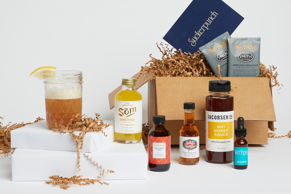 A box of Smith Teamaker teas, Som cordials, honey, tinctures, and more sits on a table next to a cocktail