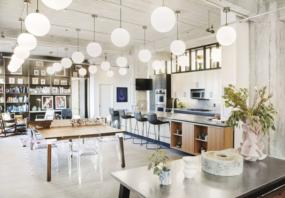 A kitchen and dining area. There is a wooden table and a kitchen island. There are multiple assorted chairs. Round light fixtures hang from the ceiling. Against the wall is white kitchen cabinetry.
