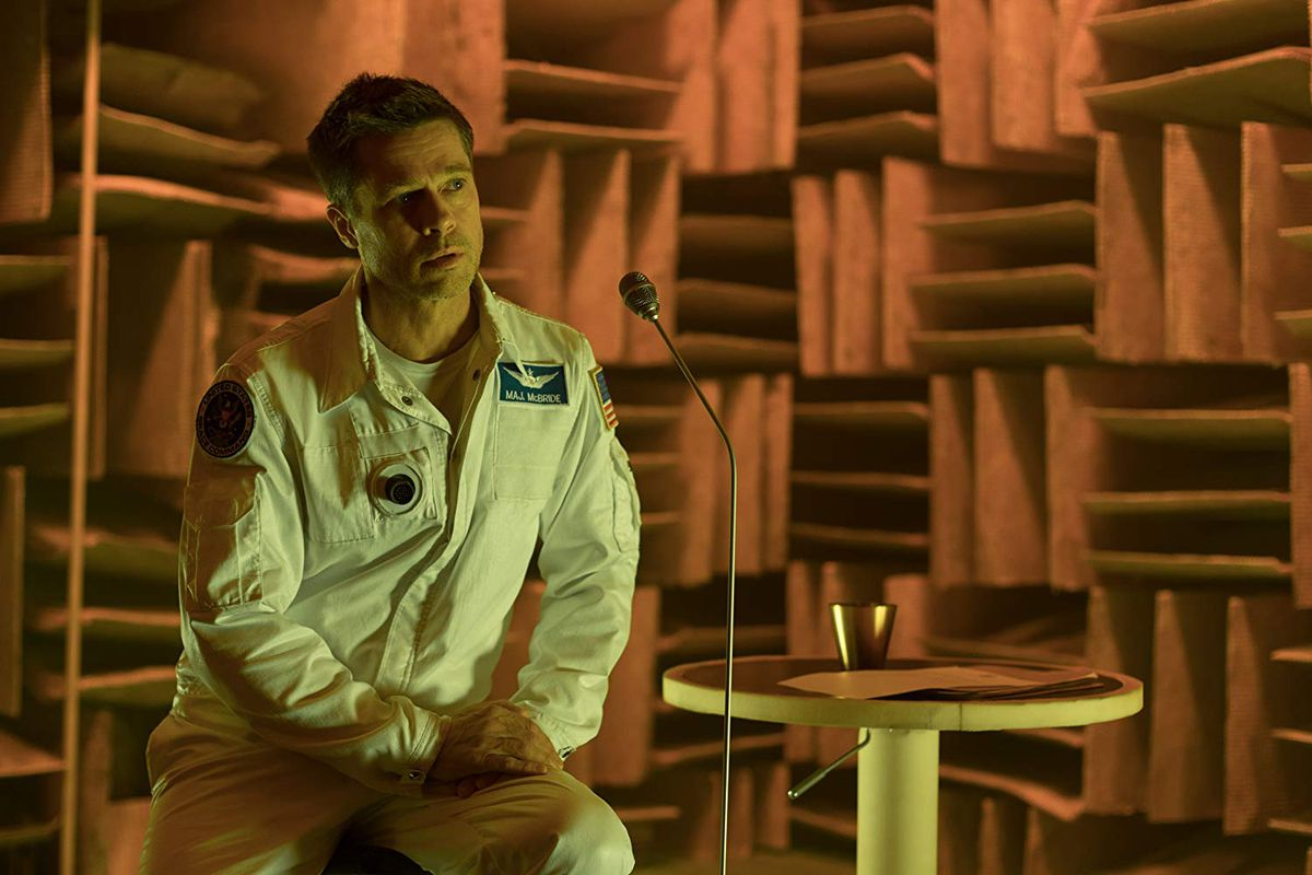 """Brad Pitt sits onstage in front of a microphone in the movie """"Ad Astra."""""""