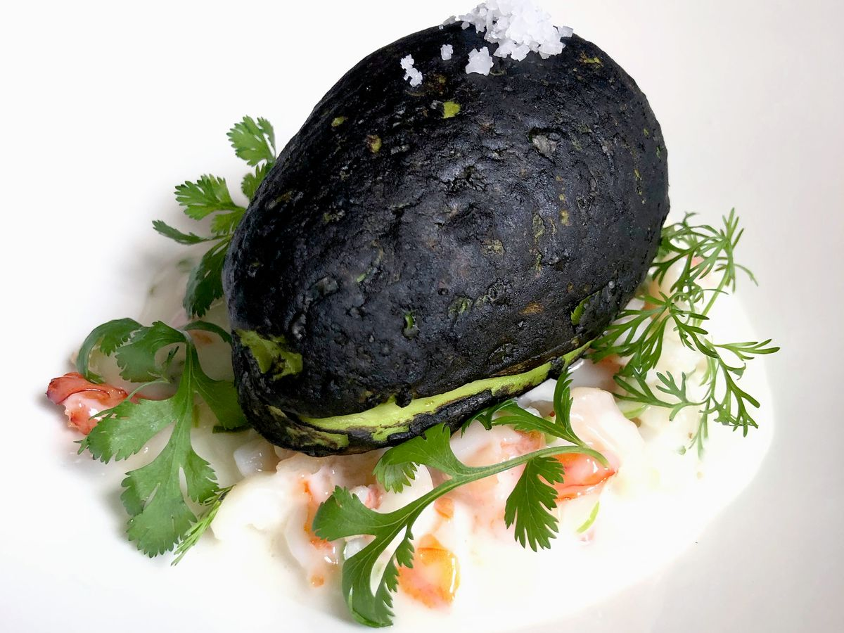 A halved avocado with fancy garnishes on a white plate.