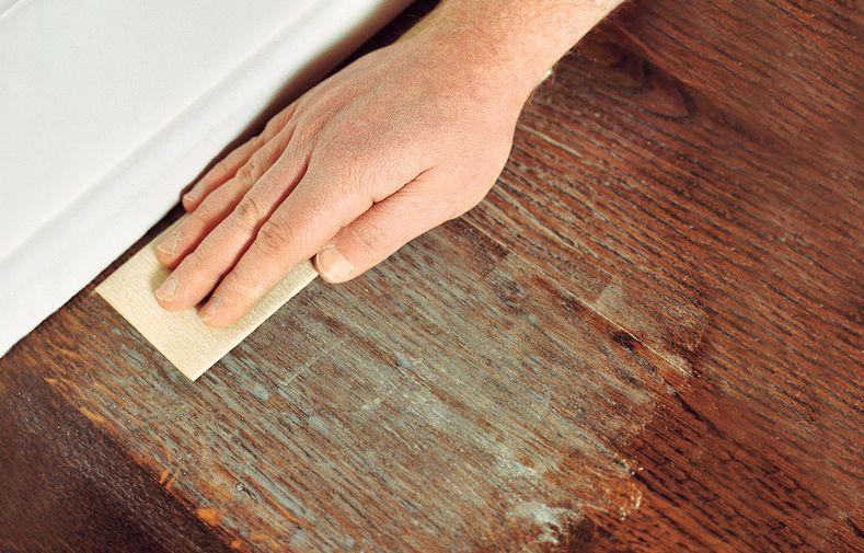 Man Hand-Sanding Perimeter Of Hardwood Floor With SandPaper