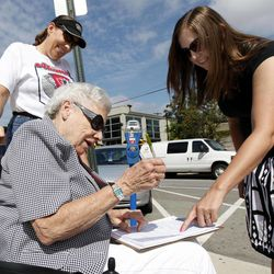 In this Sept. 9, 2011, photo, Mellissa Brown, right, a volunteer for Organizing for America, shows Barbara Ferret, center, of Westerville, Ohio, where to sign a petition, in a ballot repeal effort by opponents of the Ohio's new elections law, in Columbus, Ohio. After years of expanding when and how people can vote, state legislatures now under new Republican control are moving to trim early voting days, beef up identification requirements and put new restrictions on how voters are notified about absentee ballots. Lorraine Ferret, top left, looks on.