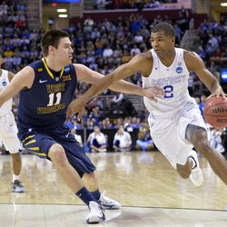 Kentucky's Aaron Harrison (2) drives on West Virginia's Nathan Adrian (11) during the first half of a college basketball game in the NCAA men's tournament regional semifinals, Thursday, March 26, 2015, in Cleveland. Harrison worked out for the Jazz on Friday.