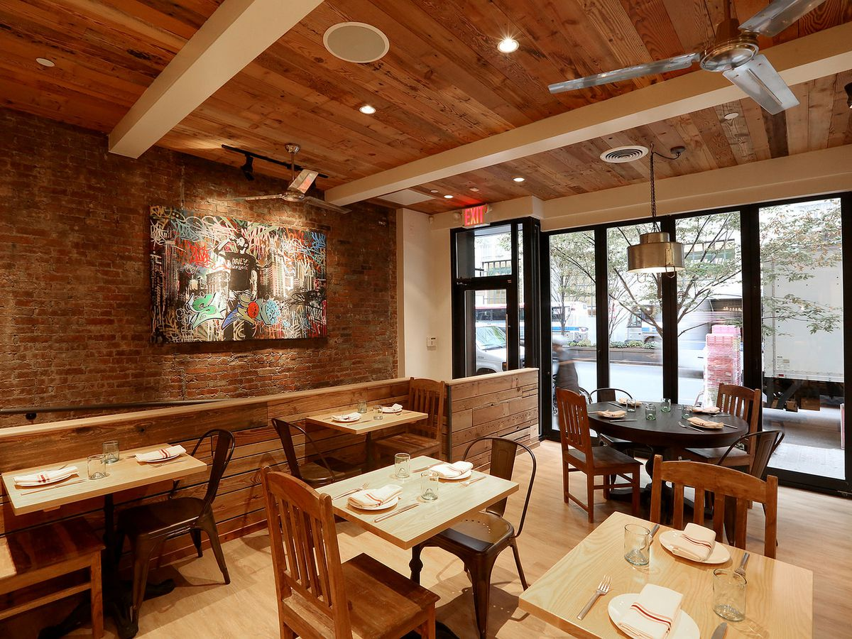 A warm, wooden dining room with wood paneling, wooden chairs, and an exposed brick wall.