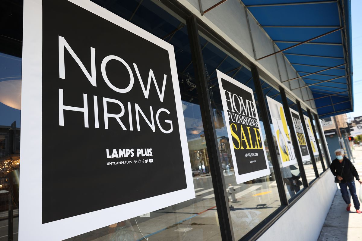 """A """"now hiring"""" sign outside of a store."""
