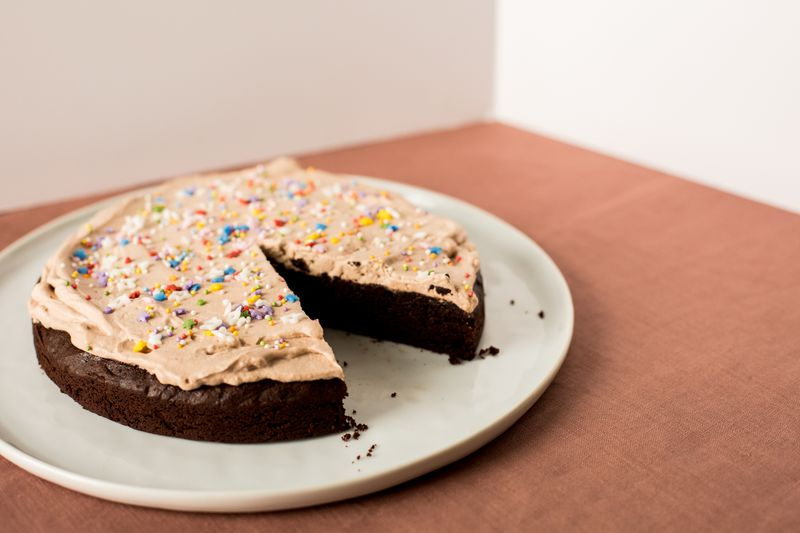 Circular chocolate cake with light brown whipped cream and sprinkles on top; one slice has been taken out.