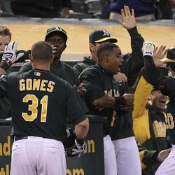 Oakland Athletics' Josh Donaldson, right,  and Jonny Gomes (31) celebrate Donaldson's two-run home run hit off Boston Red Sox's Aaron Cook in the second inning of a baseball game Friday, Aug. 31, 2012, in Oakland, Calif.