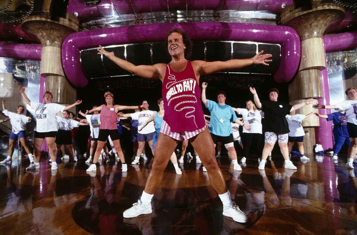 A flamboyant fitness instructor wearing a pink tank top and striped white and pink mini-shorts stands with his arms stretched wide in front of a group fitness class mirroring his movement.