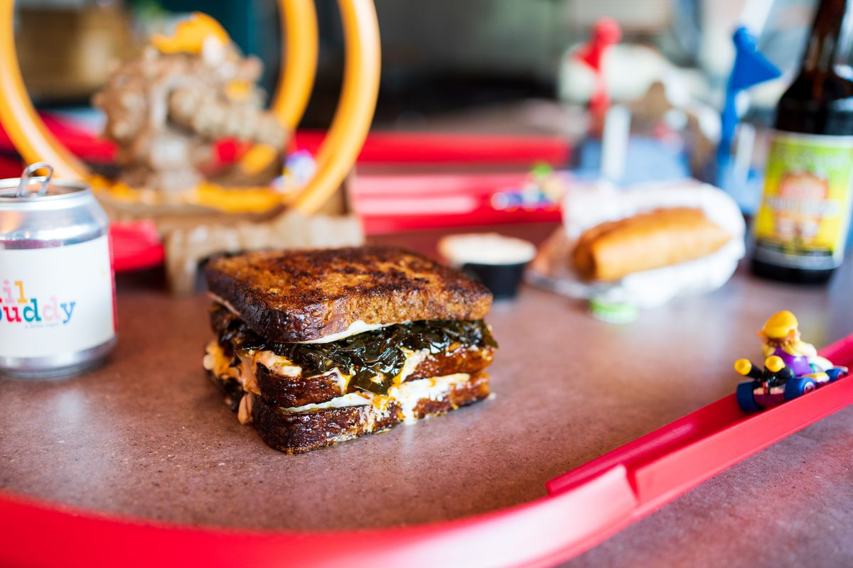 A large, gooey sandwich sits beside red toy tracks and Lego people.