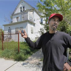 In this April 17, 2012, photo, Antie Moore stands in front of the former home of Jennifer Hudson and her family in the Englewood neighborhood of Chicago. Moore, a longtime Englewood resident, says crime is rampant in the community and that since the slayings of Hudson's family members, vandals have broken into the Hudson house at least twice to steal construction material. Opening statements begin in the murder trial of William Balfour on Monday, April 23.