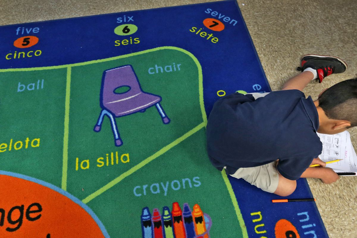 A first grader does his work while sitting on a bilingual rug at Enlace Academy, Tuesday, April 14, 2014.  The charter school, with 55 percent English-language learners, uses a blended language learning approach.