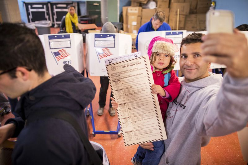 A man takes a selfie with his child as he waits to vote at a polling station in New York