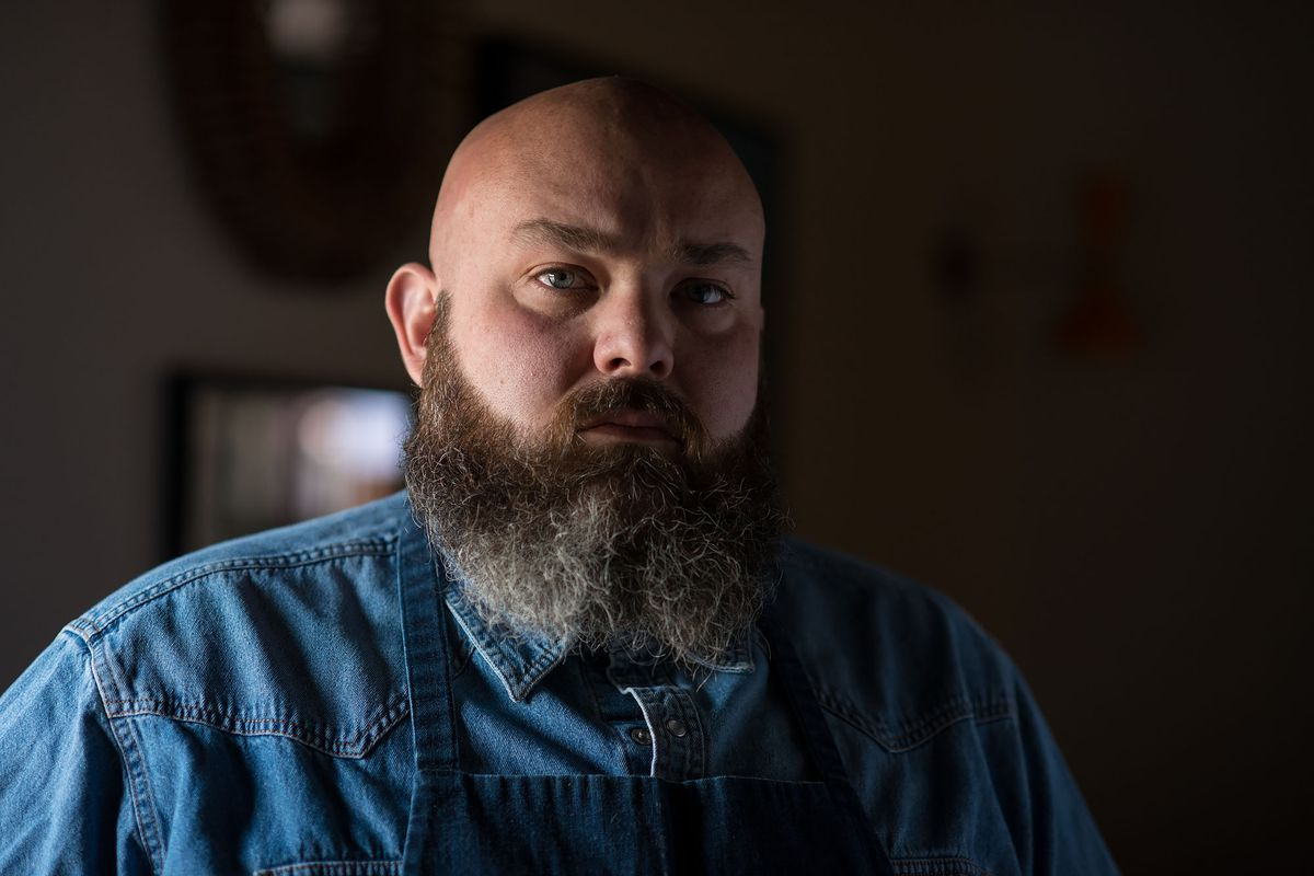 Chef Evan Funke stands looking at the camera with a large beard and stern eyes.