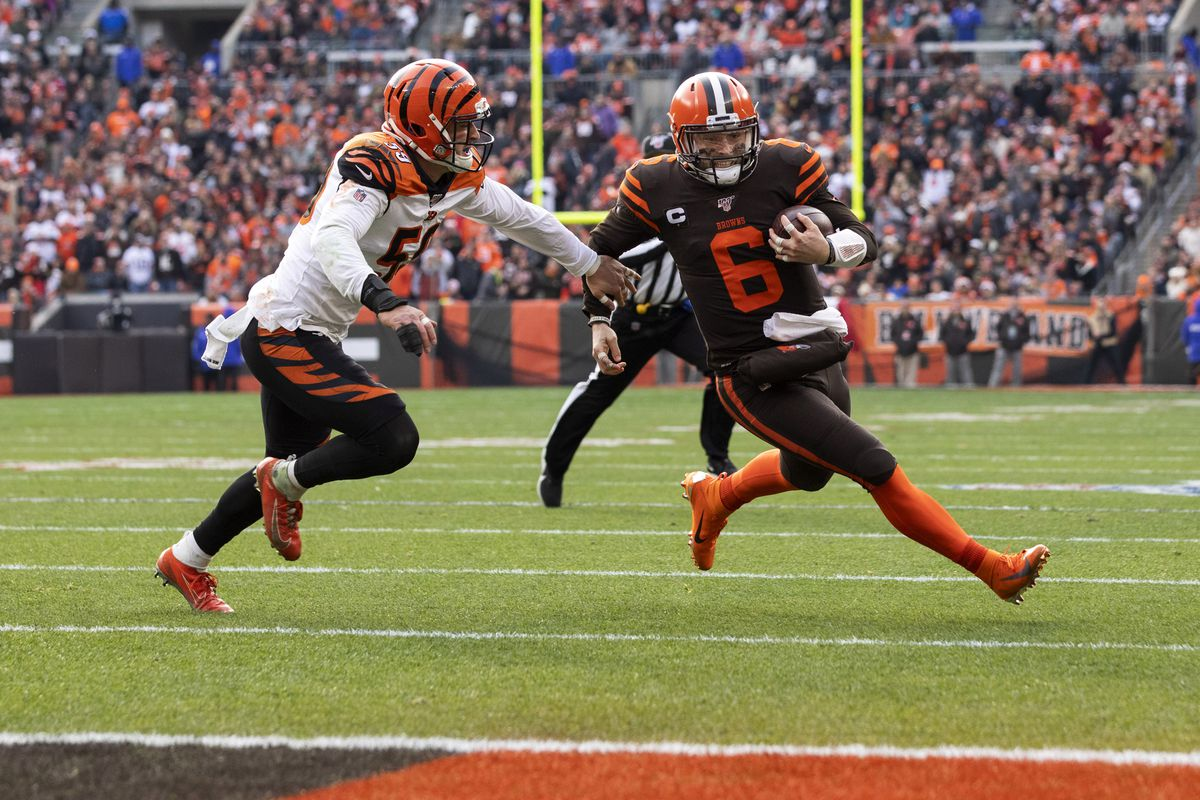 Cleveland Browns quarterback Baker Mayfield runs the ball past Cincinnati Bengals outside linebacker Nick Vigil into the end zone for a touchdown during the second quarter against the Cincinnati Bengals at FirstEnergy Stadium.
