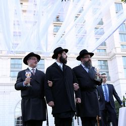 Rabbi Avraham Cohen, left, and Rabbi Benny Zippel, right, stand with Rabbi Mendy Cohen, the groom, as he waits for his bride, Chaya Zippel, during a traditional Chabad Lubavitch Jewish wedding at the Grand America Hotel in Salt Lake City on Monday, Sept. 12, 2016.