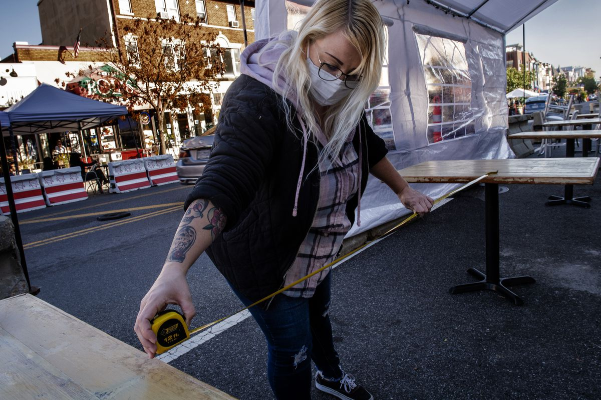 Jessica Bauer measures the distance between tables being placed beneath a new plastic tent in front of Roofers Union on 18th Street NW