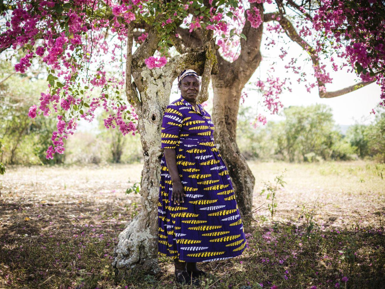 A Kenyan woman standing outside under a flowering tree.